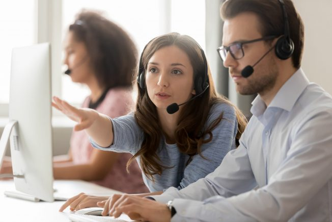 Call center employees wearing headset using computer, woman explains show to new colleague marketing database program, busy service phone operators sitting at shared desk, assistance teamwork concept